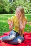 Hållande mobiltelefon för blond flicka och lyssnande musik med headphon Arkivbilder