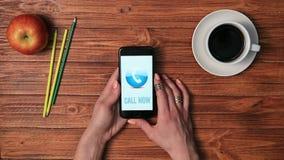 Hållande mobiltelefon för flicka med APPELL NU på skärmen lager videofilmer