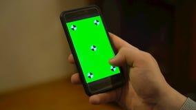 Hållande mobiltelefon för hand med den gröna skärmen arkivfilmer