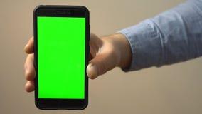 Hållande mobiltelefon för hand med den gröna skärmen lager videofilmer