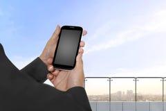 Hållande mobiltelefon för hand med den tomma tomma skärmen Royaltyfri Foto