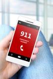 Hållande mobiltelefon för hand med nöd- nummer 911 Fotografering för Bildbyråer