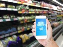 Hållande mobiltelefon för hand med online-shoppingord Arkivfoto