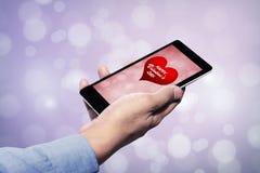 Hållande mobiltelefon för hand med valentin dagönska Royaltyfri Bild