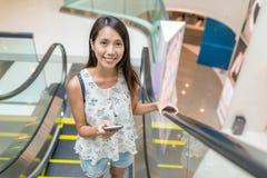 Hållande mobiltelefon för kvinna på rulltrappan i shoppinggalleria Arkivbild