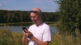 Hållande mobiltelefon för lycklig man och smsande meddelande i sommarskog med sjön lager videofilmer