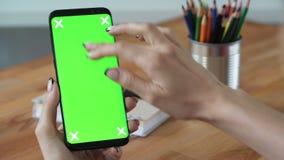 Hållande mobiltelefon för person med grön skärmskärm i hand lager videofilmer