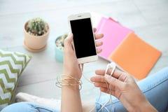 Hållande mobiltelefon för ung kvinna med skärmen och hörlurar i händer, inomhus arkivbilder