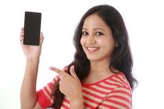 Hållande mobiltelefon för ung kvinna mot vit Arkivbilder