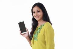 Hållande mobiltelefon för ung kvinna mot vit bakgrund Royaltyfria Foton