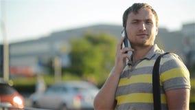 Hållande mobiltelefon för ung man, genom att använda smartphonen och att göra en appell och att tala på telefonen som står på den arkivfilmer
