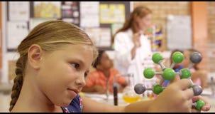 Hållande molekylmodell för skolflicka i laboratorium arkivfilmer