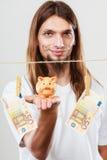 Hållande moneyboxpiggybank för man Arkivbilder