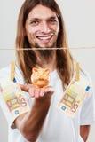 Hållande moneyboxpiggybank för man Royaltyfri Bild
