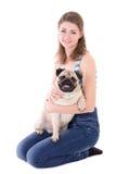 Hållande mopshund för ung kvinna som isoleras på vit Fotografering för Bildbyråer