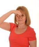 Hållande näsa för kvinna royaltyfri foto