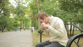 Hållande näsduk för ung man på näsa en man har en dålig förkylning arkivfilmer