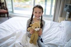 Hållande nallebjörn för flicka på säng i sovrum Fotografering för Bildbyråer