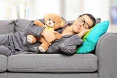 Hållande nallebjörn för ung man och ta en ta sig en tupplur på soffan Royaltyfri Foto