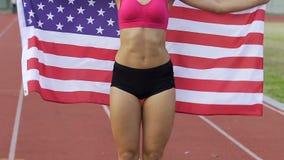 Hållande nationsflagga för glad idrottskvinna och fröjdseger i konkurrens stock video