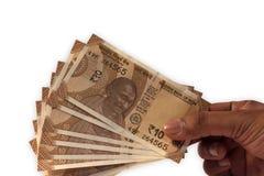 Hållande ny indier 10 rupie valutaanmärkningar i hand arkivbild