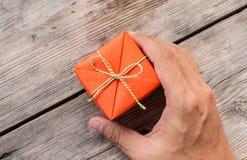 Hållande orange gåvaask för hand och gulingband royaltyfria bilder