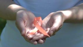 Hållande orange medvetenhetband för kvinna i händer arkivfilmer