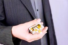 Hållande packe av cigaretter royaltyfria bilder