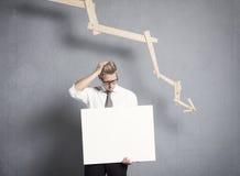 Hållande panel för frustrerad affärsman framme av att peka för graf Arkivbild