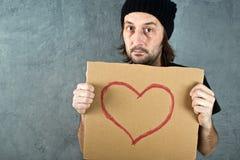 Hållande papppapper för man med hjärtaformteckningen Royaltyfria Bilder