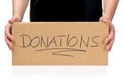 Hållande papptecken för man som kallar för donationer Arkivbilder