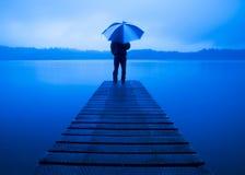 Hållande paraply för man på brygga ett stillsamt sjöbegrepp arkivbild