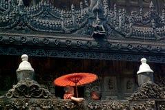 Hållande paraply för ung munk på den Shwenandaw kloster i Mandalay Arkivfoton