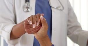 Hållande patients för afrikansk amerikandoktor hand royaltyfri foto