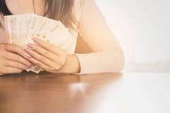 Hållande pengar för asiatisk hand för affärskvinna som hyvlar för att investera, eller betala royaltyfria foton