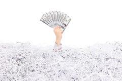 Hållande pengar för hand i en hög av strimlat papper Royaltyfria Foton