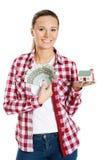 Hållande pengar för ung kvinna och ett hus förestående. royaltyfri fotografi