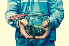 Hållande pengarkrus för man med mynt - retro stil Arkivfoto