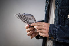 Hållande pengarräkningar för man för att spela kasinovågspel royaltyfria bilder