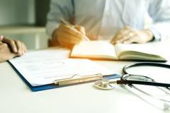 Hållande penna för doktorshand som skriver listan för tålmodig historia på anteckningsboken och talar till patienten om läkarbeha royaltyfria bilder