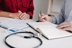Hållande penna för doktorshand som skriver listan för tålmodig historia på anteckningsboken och talar till patienten om läkarbeha arkivbild