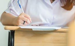 Hållande penna för flickastudenter som tar examina som skriver undersökningsrum Arkivfoton