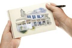 Hållande penna för händer och block av papper med husteckningen Royaltyfri Fotografi