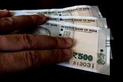 Hållande person ut den nya indierRs 500 anmärkningen Arkivfoto