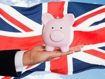 Hållande piggybank för brittisk affärsman Arkivfoto