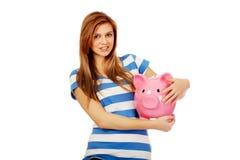 Hållande piggybank för lycklig tonårs- kvinna Royaltyfria Bilder