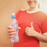 Hållande plast- flaska för ung smilinglkvinna tum upp fokuserat Royaltyfri Foto