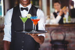 Hållande portionmagasin för bartender med coctailexponeringsglas royaltyfri fotografi