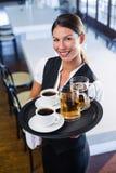 Hållande portionmagasin för servitris med kaffekoppen och den halv literen av öl Royaltyfri Bild