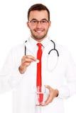 Hållande preventivpiller för doktor och exponeringsglas av vatten Fotografering för Bildbyråer